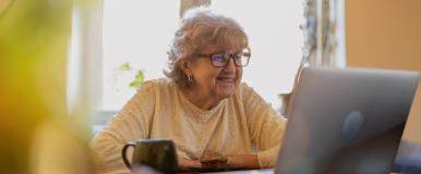 Woman using computer with mug of coffee